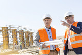 Fototapety Male engineers discussing at construction site against clear sky