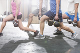 Fototapety Low section of people lifting kettlebells at crossfit gym