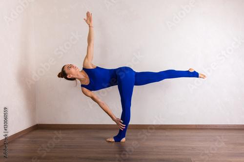 Tuinposter Gymnastiek Young beautiful woman practicing yoga at home