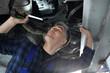 Auto naprawa. Samochód w warsztacie, mechanik sprawdza stan podwozia.