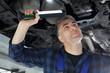 Samochód w warsztacie, mechanik sprawdza stan podwozia.