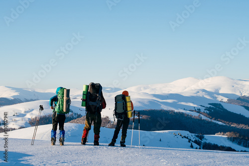 Poster Three tourists with backpacks standing on top of a mountain and