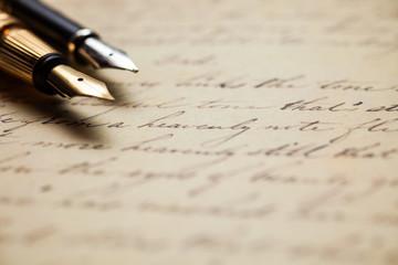 Fountain pens on an antique handwritten letter