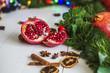 Постер, плакат: Разрезанный красный гранат корица сушеные лимоны лежат на белом деревянном столе на фоне зеленой новогодней гирлянды и новогодних огней