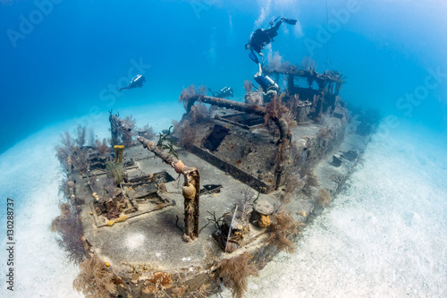 In de dag Schipbreuk SCUBA Divers Swimming Around an Old, Coral Encrusted Shipwreck