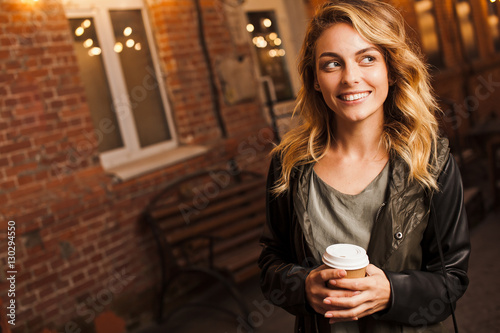 Young attractive woman with coffee to go outdoors on street Poster