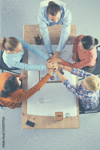 Poster Closeup of a business colleagues with their hands stacked