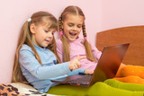 Two girls include laptop at work, sitting on the bed