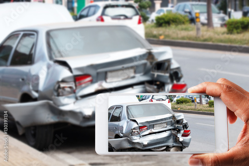 Close up hand holding smartphone and view photo of car accident Poster