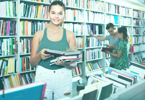 portrait of  teenage girl customer looking at open book standing Poster