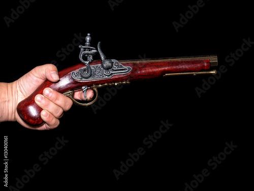 Zdjęcia Vintage pistol in hand holding on black background - Prussian antique flintlock pistol with copy space