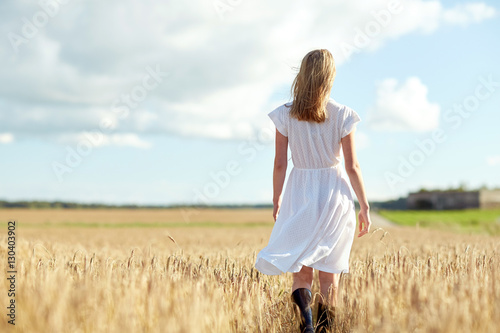 Plagát young woman in white dress walking along on field