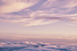Abstract background with pink, purple and blue colors clouds. Sunset sky above the clouds. Dreamy fantasy background in soft pastel colors.