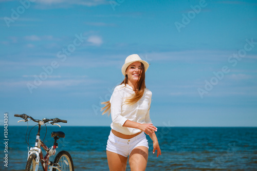Girl with bike on beach. Poster