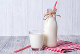 Fototapety Bottle and glass of milk with red straw, white wooden background