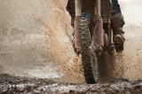 Fototapety Motocross driver splashing mud on wet and muddy terrain