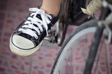 Person riding a vintage bicycle, close up view of sneaker shoe a