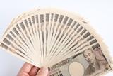 たくさんの一万円札を持つ手