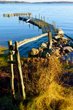 Calm and motionless water surround some piers in the archipelago. The morning winter sun is slowly thawing the grass. Location Kuggeboda near Ronneby in Sweden.