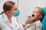Woman dentist in mask doing teeth checkup of little girl in dental room. Health care and medicine concept.   - 130534705