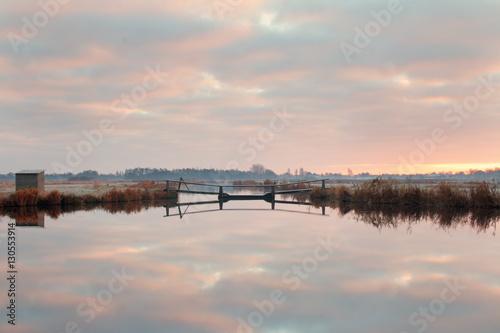 Poster Weerspiegeling van zonsopkomst in poldersloot met bruggetje