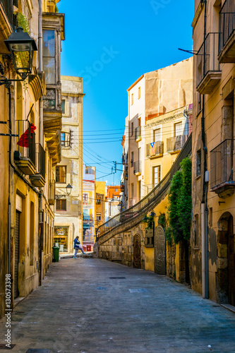 people are strolling through a colorful narrow street in the historical center of spanish city tarragona
