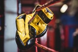 Yellow boxing gloves hanging off the boxing ring - 130576929