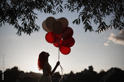 Poster Red-haired girl with red and white balloons in nature against the sky