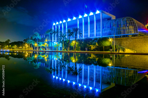 View of the palau de la musica de valencia concert hall reflecting in a pond during night.