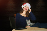 girl holding a cat on her lap in a red Santa hat with a laptop
