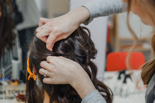 Stylist curling hair and making wedding hairstyle for brown haired woman Slika na platnu