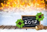 2017 Silvester bokeh Hintergund mit Sektfkorken Tafel Grüßen und Wünschen im Schnee auf Holzboden