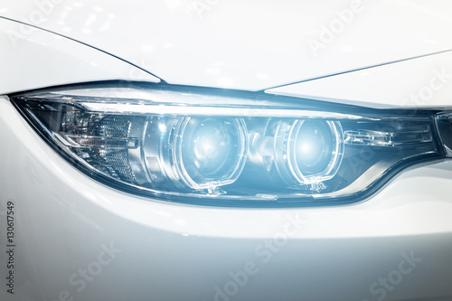Closeup headlights of modern car during turn on light in night. плакат