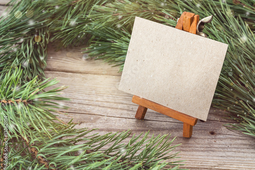 Miniature easel with blank card and pine branches.