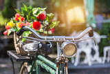 close up vintage bicycle with bouquet flowers in basket in vintage tone style