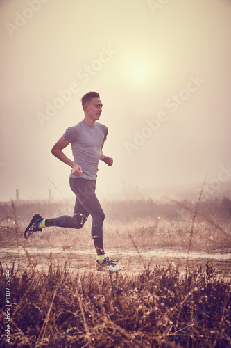 Ragazzo atletico si allena all'aperto su terra di sera Poster