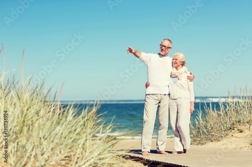 Poster happy senior couple hugging on summer beach
