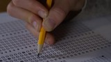 4K Young female marking her test answers on paper with a pencil