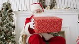 Santa Claus looking at the camera and teasing with a present