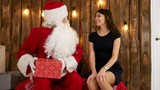 Santa Claus giving a nicely wrapped present to a beautiful young woman in black dress