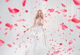 Pretty, elegant blonde dancing among rose petals