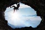 Climber w wysokich górach na wyjściu z jaskini