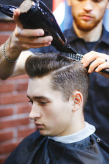 Male barber makes hair styling using a dryer.