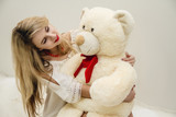 Attractive blonde girl with beautiful eyes sits on her bed and hugging a Teddy bear. Woman in light white dress. Sexy lady