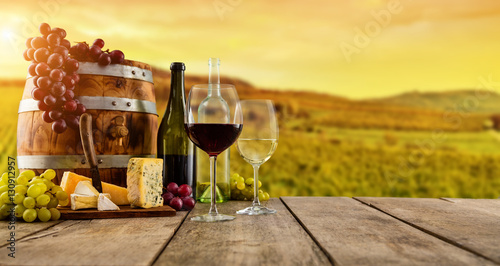 Fototapeta Red and white wine served on wooden planks, vineyard on background