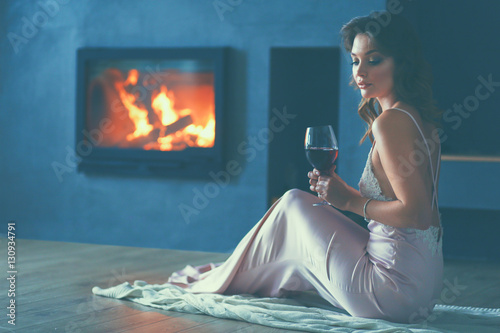 Poster Woman with a glass of wine by the fireplace