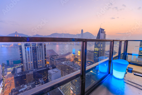 Hong Kong, China - January 1, 2016: spectacular aerial view of Victoria Harbor skyline at sunset from the rooftop of Eye Bar, a modern skybar inside iSquare shopping center in Kowloon, Hong Kong city.