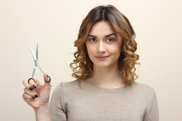 Young beautiful girl holds a professional shears.