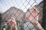 Refugee hands keeping metal fence mesh - 130975777