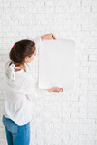 Young woman looking at empty sheet of paper, mockup. Female holding blank poster and reading information on it, copy space for text or advertisement. Promo, warning message concept - 130996751